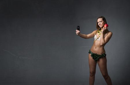 eve taking selfie with apple, dark background