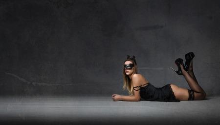 girl wiht mask lying down on the floor, dark background Stock Photo