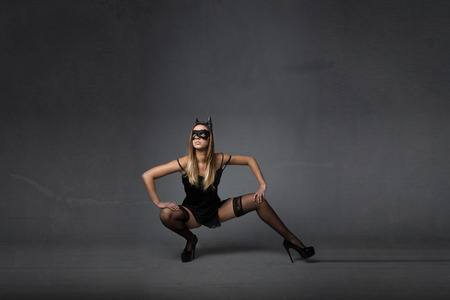 model with mask squat pose, dark background