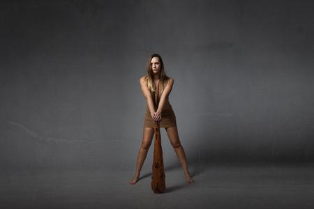 neanderthal women: prehistoric man with club, dark background