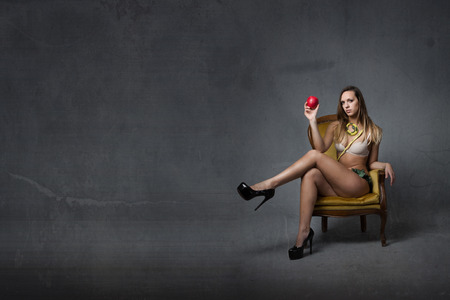 Eve biblical character with red apple, dark background Stock Photo
