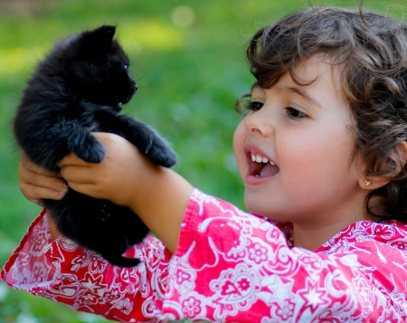 kid with a baby black cat Stock Photo