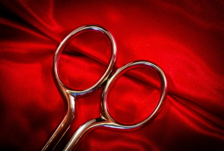 steel scissors on red fabric photo