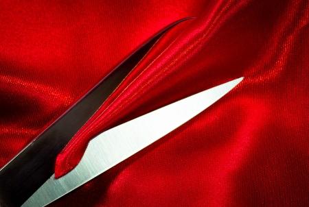 tijeras de acero en tela roja