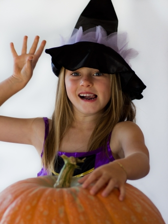 little witch with pumpkin in haloween party photo