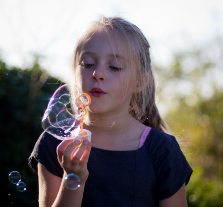 little girl playing with soap bubbles in nature photo