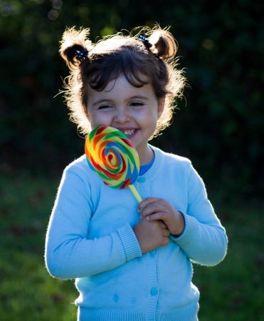 little girl with lollipop candy in nature photo