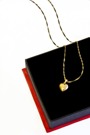 golden chain with a golden heart in a black and red box photo