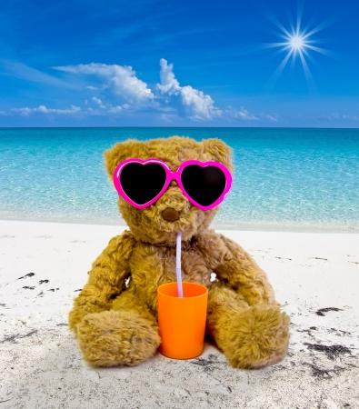 oso de peluche tomando el sol en una playa tropical y beber Foto de archivo