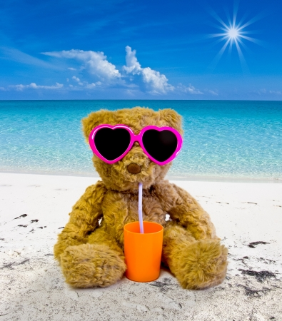 teddy bear sunbathing on a tropical beach and drinking Stock Photo
