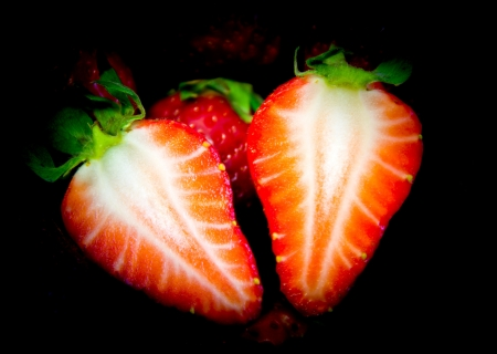 cut strawberry on a black background photo