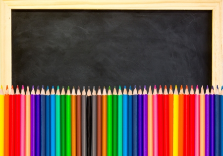 back to school: colored pencils on black chalkboard background
