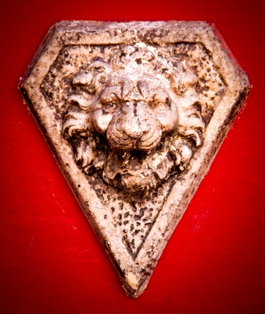 carving: stone lion head in a red wall