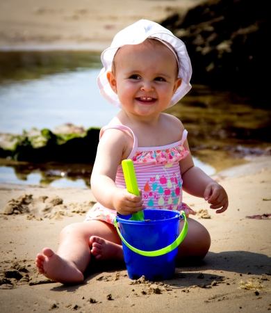 portrait of a little baby playing on the beach photo
