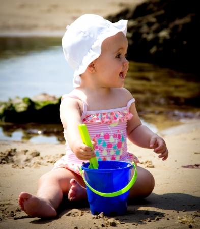 klein meisje op strand: portret van een kleine baby spelen op het strand