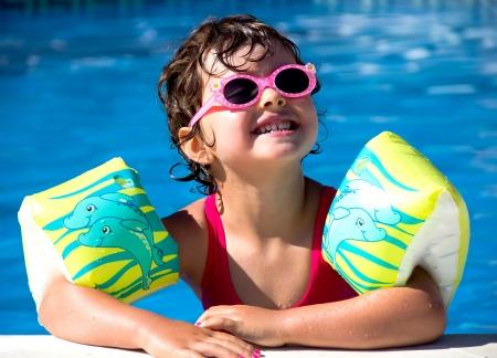 フロート付きプールで泳いでいる少女 写真素材