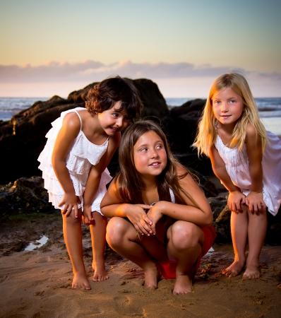 tres ni�as en una puesta de sol en la playa Foto de archivo