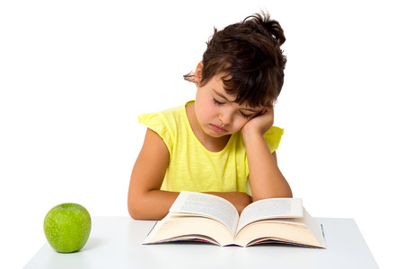 little girl reading a book with apple isolated on white photo