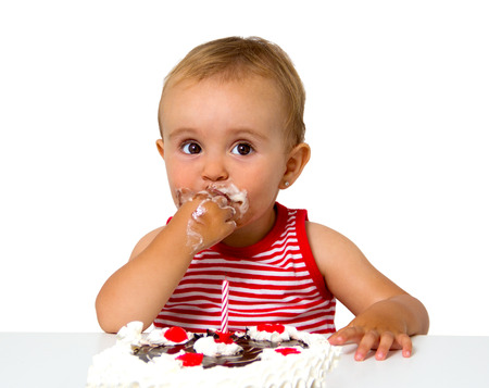 eat smeared: baby with birthday cake isolated on white