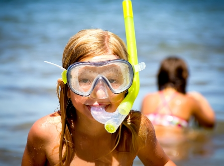 portrait of a little girl on the beach with a diving mask Stock Photo