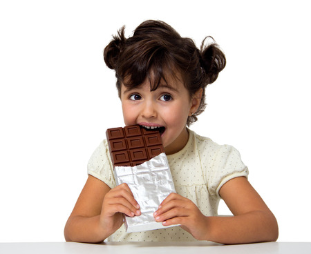 白で隔離チョコレートを食べる少女 写真素材