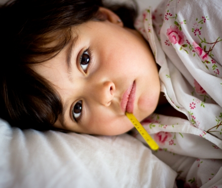 enfant malade: portrait d'une petite fille avec un thermomètre dans le lit