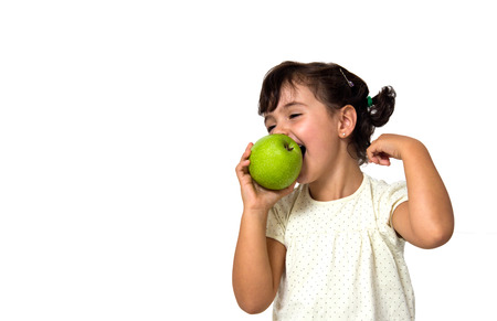 portrait of a little girl eating apple isolated on white photo