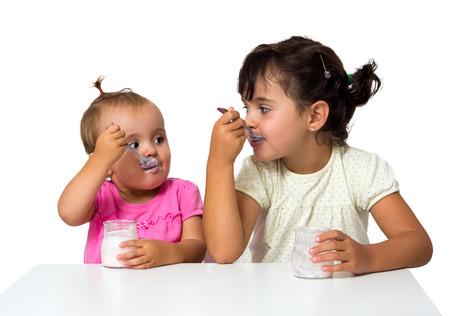 2 つの小さな女の子を白で隔離されるヨーグルトを食べる
