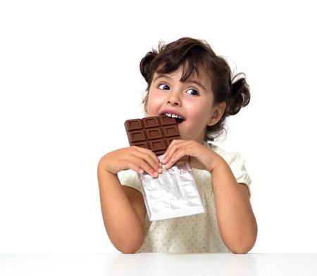 白で隔離されるチョコレートを食べる少女
