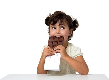 little girl eating chocolate isolated on white