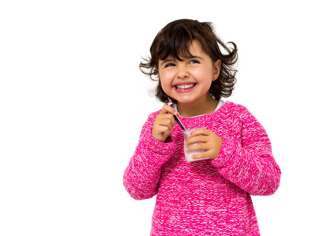 girl eating yogurt isolated on white photo
