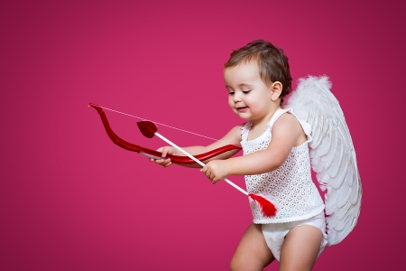 baby cupid with a bow, arrow and wings photo