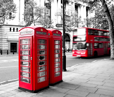 red phone booth and red bus in motion. London