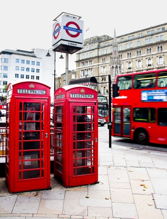 London, October 2013 - red phone booth, the underground sign and red bus in motion.