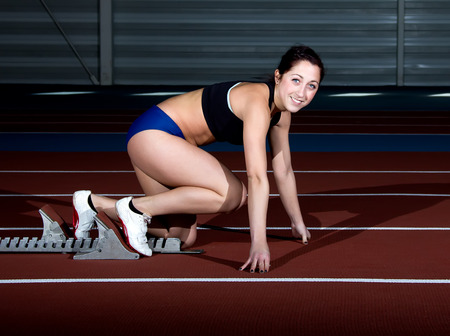 Woman sprinter leaps from starting block. photo