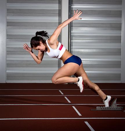 여자 육상 선수 블록을 시작 도약.