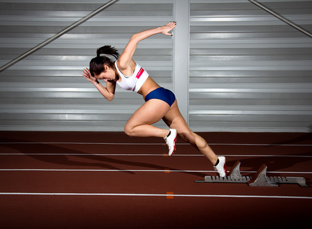 Woman sprinter leaps from starting block. Stock Photo