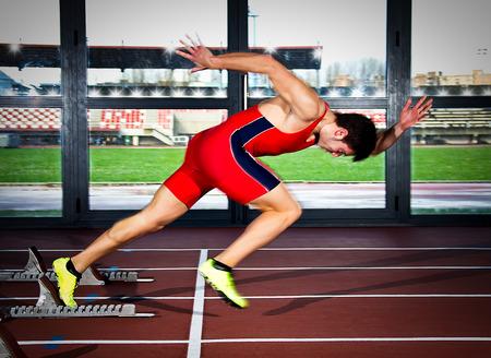 Man sprinter leaps from starting block. photo