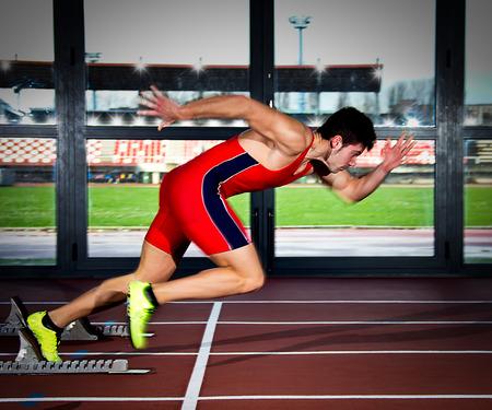 Mann springt vom Sprinter Startblock. Standard-Bild