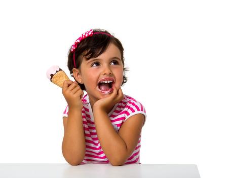 小さな女の子を白で隔離されるアイスクリームを食べる 写真素材