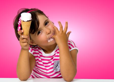 ピンクの背景でアイスクリームを食べる少女