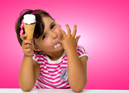 little girl eating ice cream in a pink background
