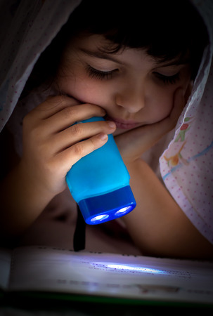 Little girl reading in bed with flashlight photo