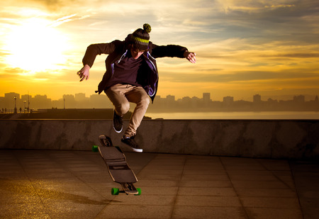young teenager jumping with a longboard photo