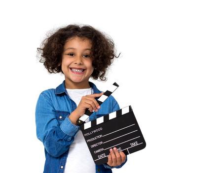 Portrait d'une petite fille avec une ardoise de film isolé sur blanc