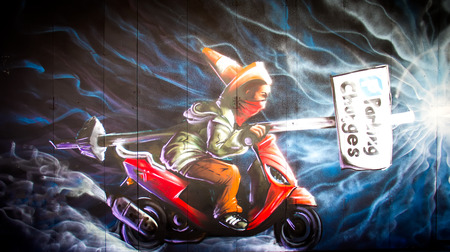 London, June 2014 - urban graffiti near Camden Lock Market. The work is a drawing portrait of man on a motorcycle by an unknown artist Editorial