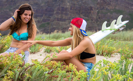 Pretty surfer girls on the beach with surfboard photo