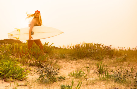 Pretty surfer girl on the beach with surfboard photo