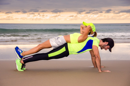 Young couple runners training on the beach Stock Photo