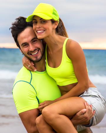 Joven pareja de corredores que entrenan en la playa